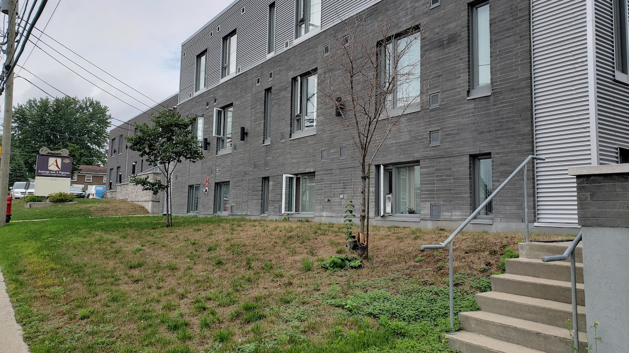 L'extérieur d'un établissement pour aînés, aux briques grises, en été.