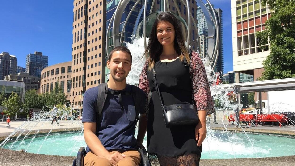 Un couple pose devant une fontaine au centre-ville de Vancouver.