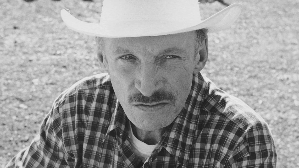 L'homme est vêtu d'un chapeau blanc et d'une chemise à carreaux.