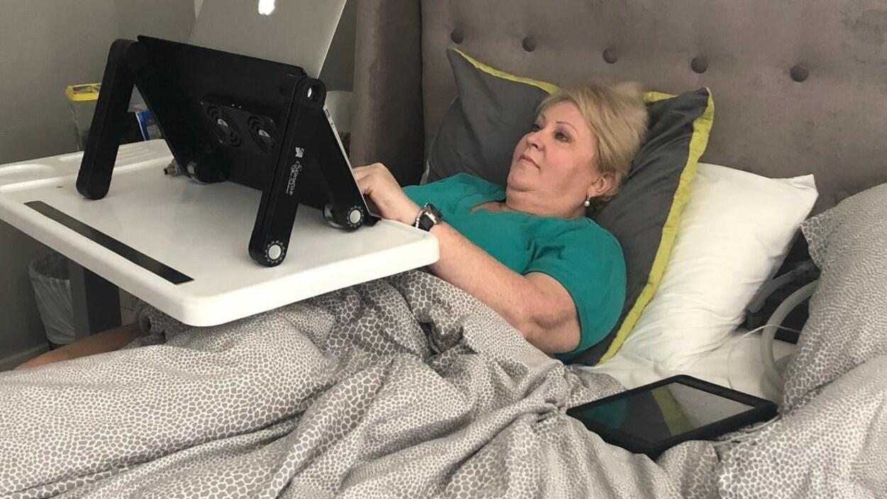 Audrey Parker lit sur un ordinateur, couchée dans son lit.