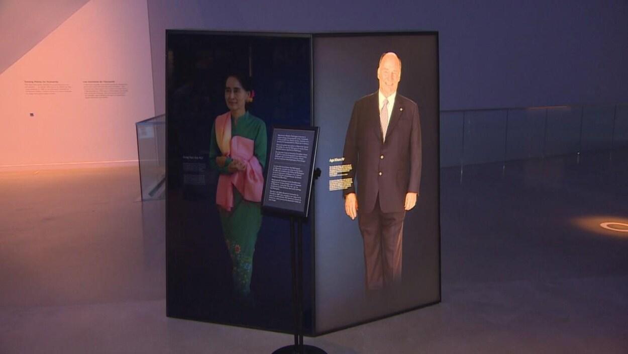 Un panneau dans une exposition portant l'image d'une femme asiatique sur son côté gauche est assombri tandis que le portrait d'un homme sur le côté droit est illuminé.