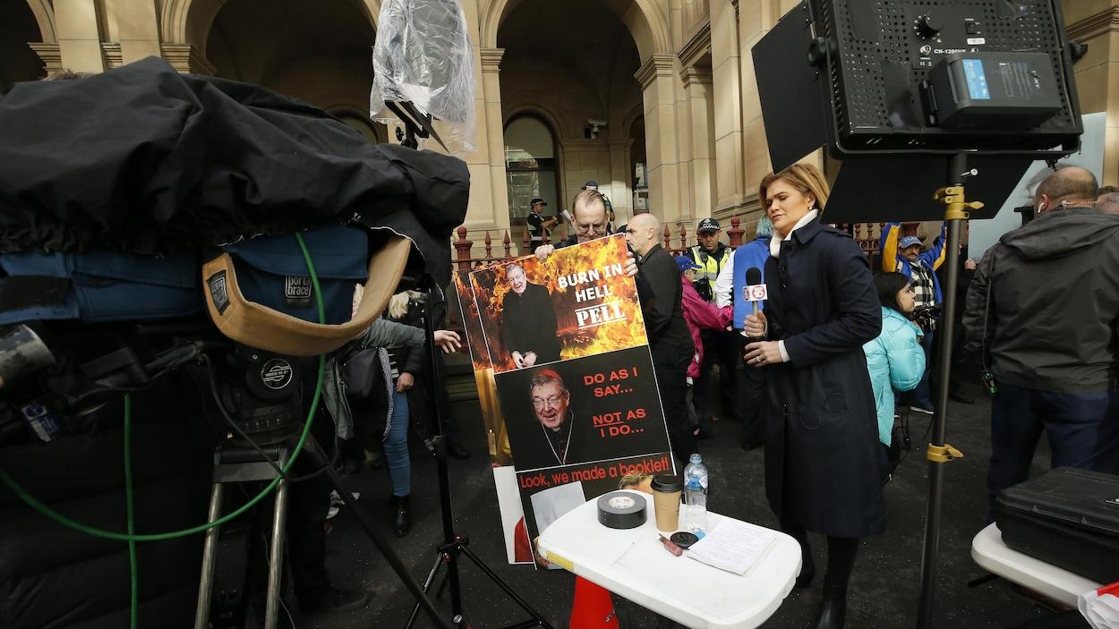 Un homme portant une pancarte et une femme portant un micro, en arrière plan des manifestants.