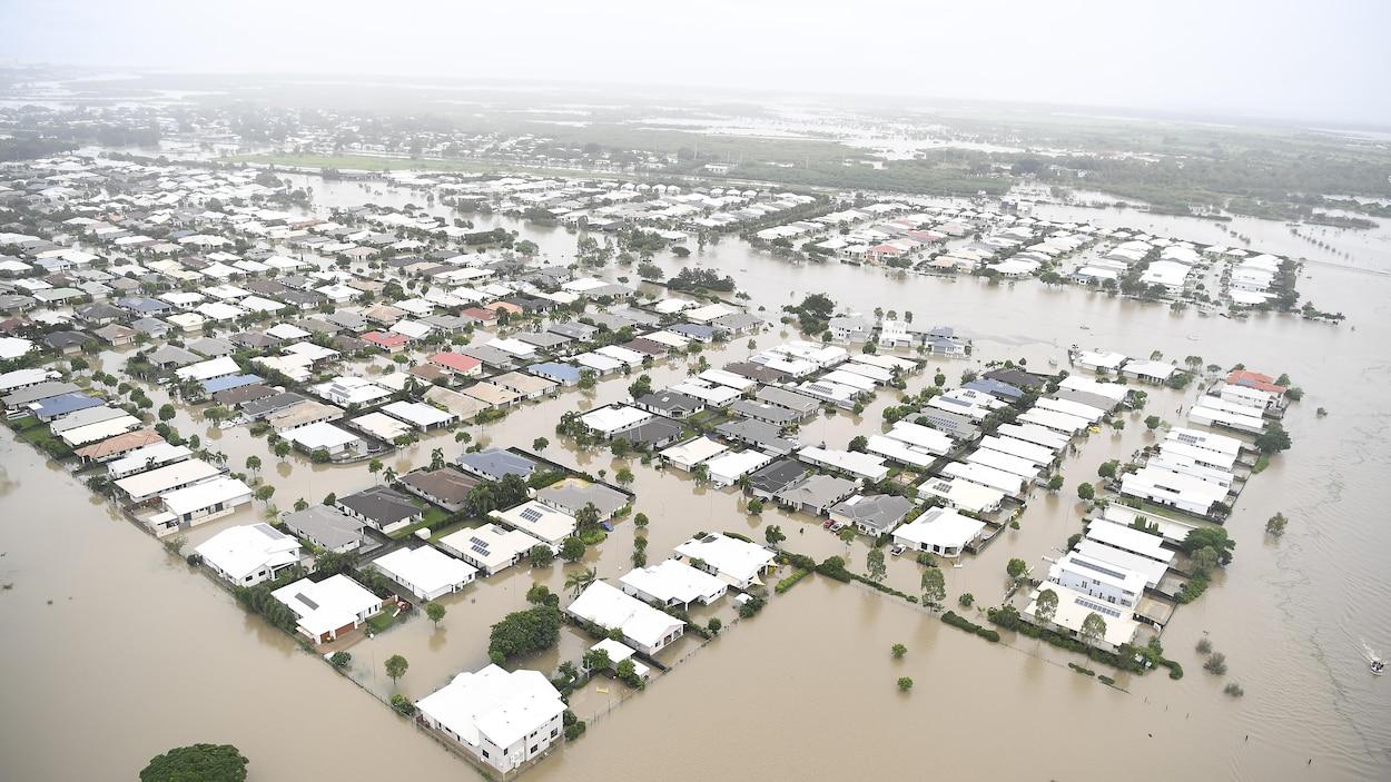 Vue aérienne d'un quartier résidentiel sous les eaux brunâtres en Australie.