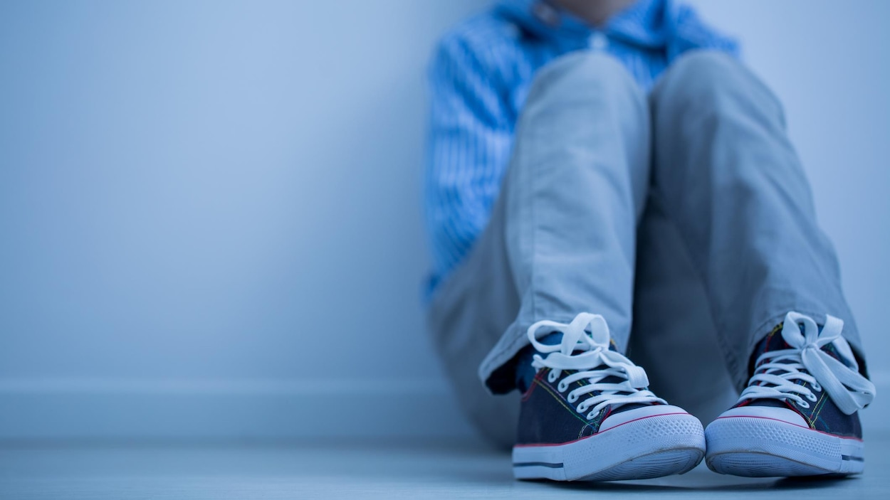 Un garçon assis seul contre un mur.
