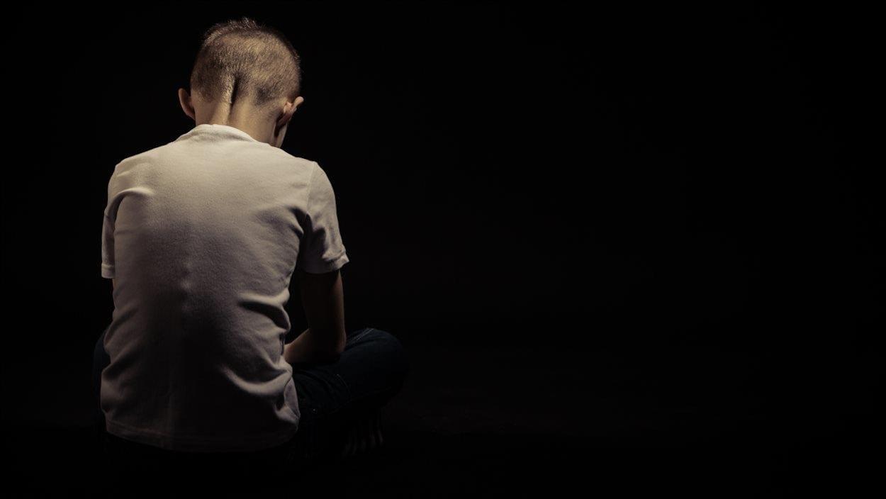 Dans un pièce noire, un enfant est vu de dos, la tête baissée.
