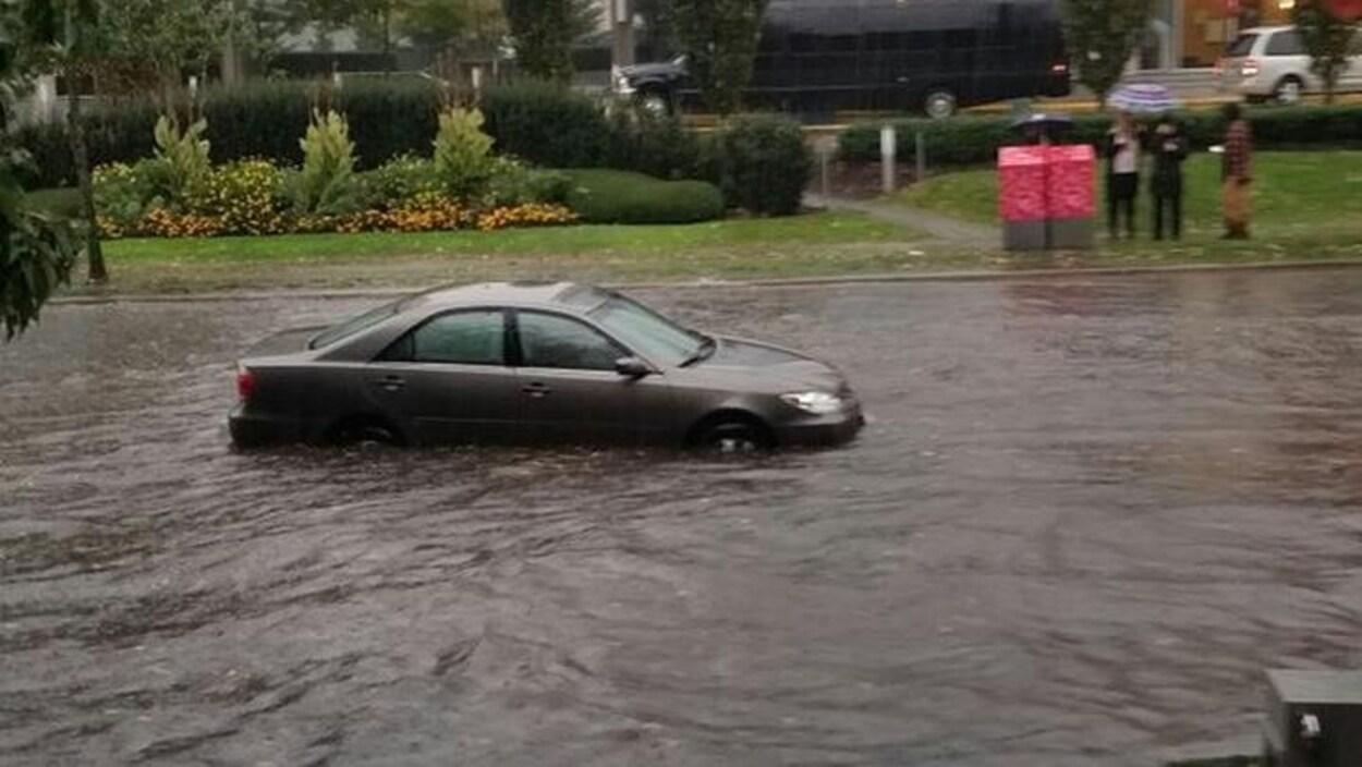 Une voiture en plein milieu d'une rue inondée alors que trois personnes l'observent du trottoir