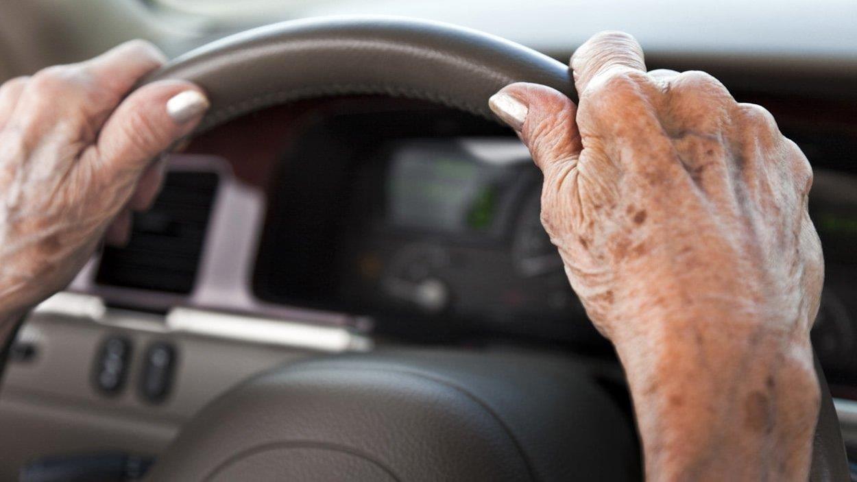 Deux mains d'une femme âgée sont posées sur le volant d'une voiture.