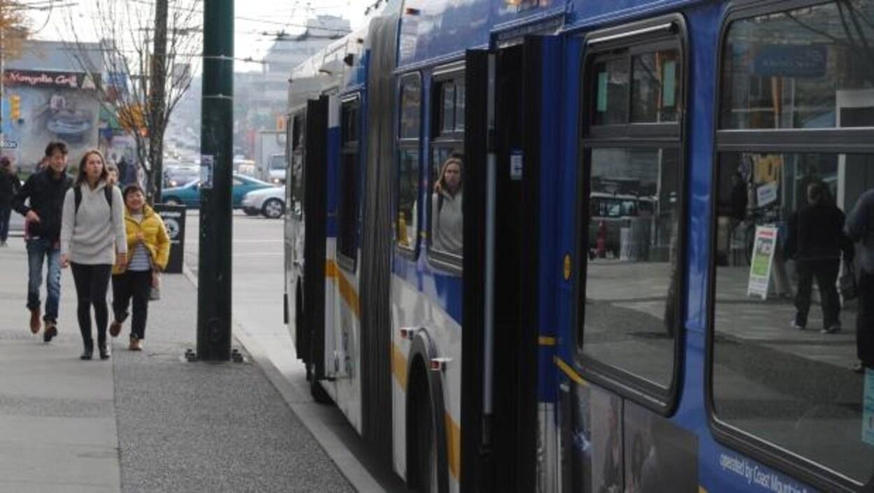 Des piétons s'approchent d'un autobus à l'arrêt dans le Grand Vancouver