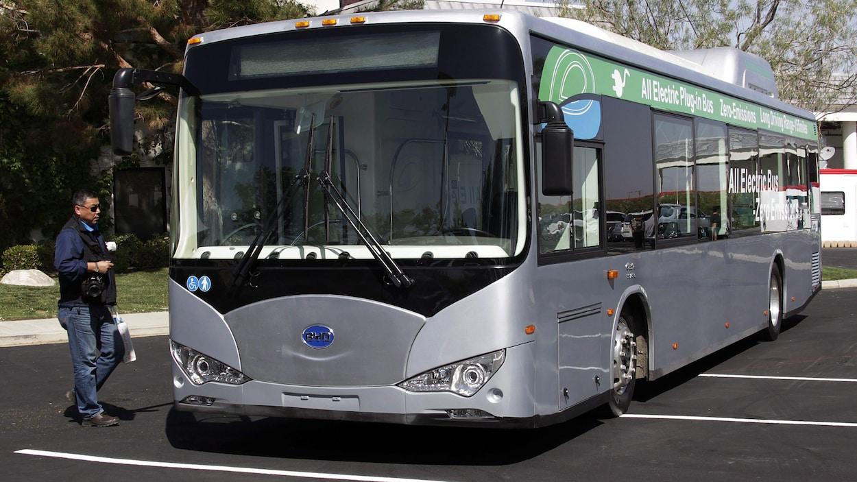 Un autobus électrique gris en montre à l'extérieur dans un terrain de stationnement.