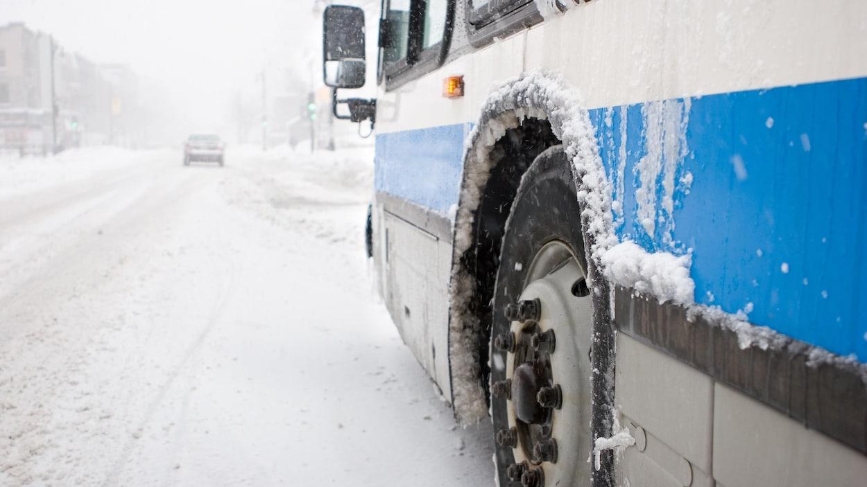 Gros plan sur la roue avant d'un autobus qui avance dans une rue enneigée.