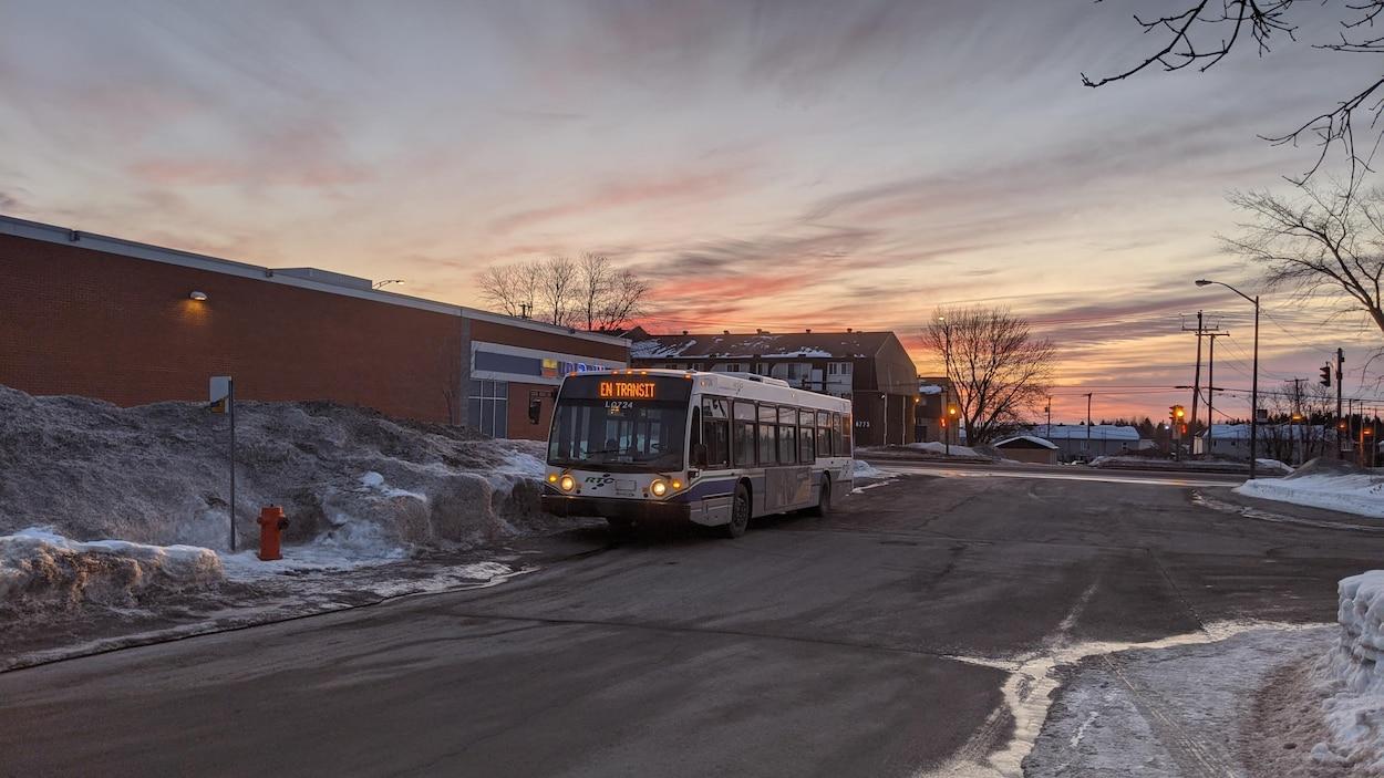 Un autobus en transit stationné près d'une pharmacie. C'est l'hiver, tôt le matin.