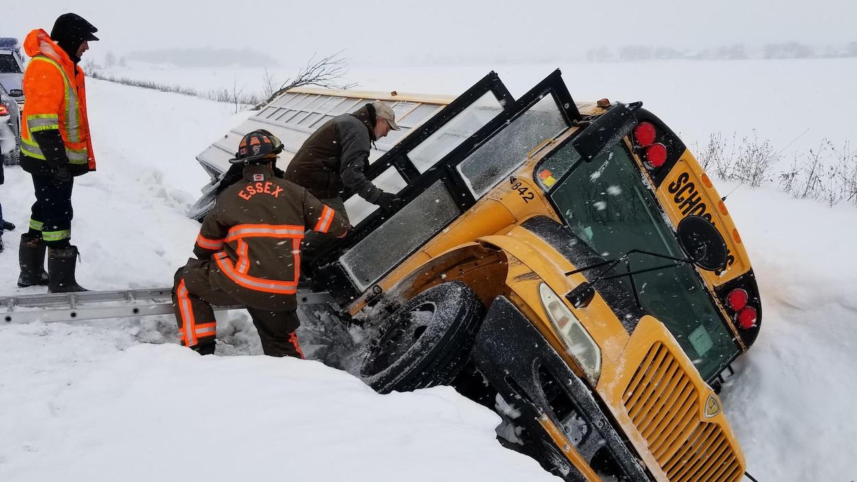 Des pompiers viennent au secours des enfants qui se trouvent dans un autobus jaune, alors que le véhicule est complètement renversé sur son côté dans un fossé enneigé.