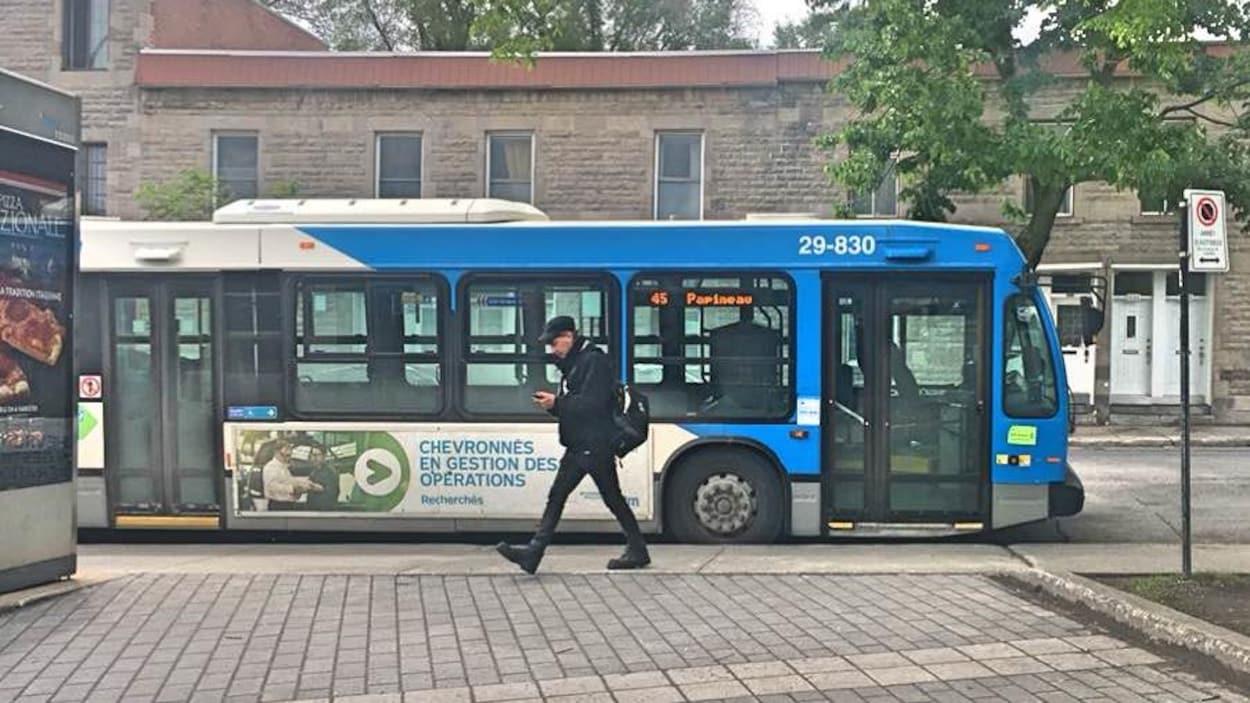Un homme marche devant un autobus en regardant son téléphone cellulaire.