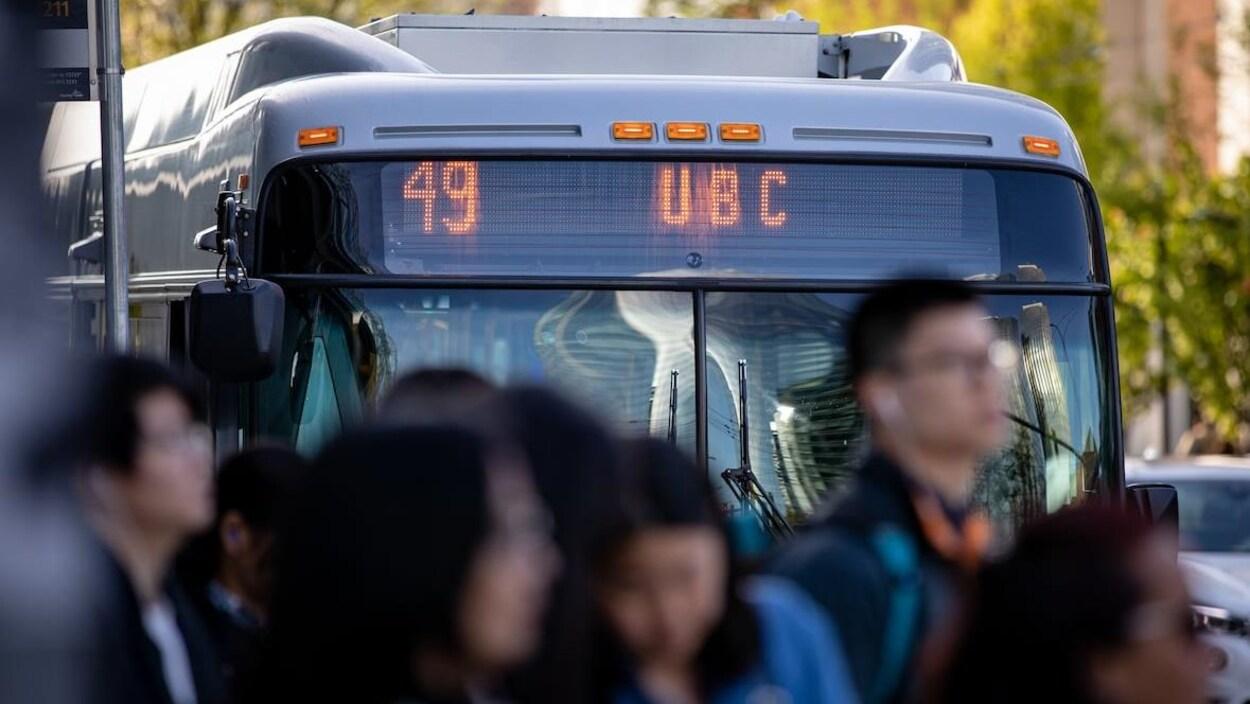 En arrière-plan, un autobus avec le numéro 49 est arrêté. En avant-plan, des gens attendent à un arrêt.