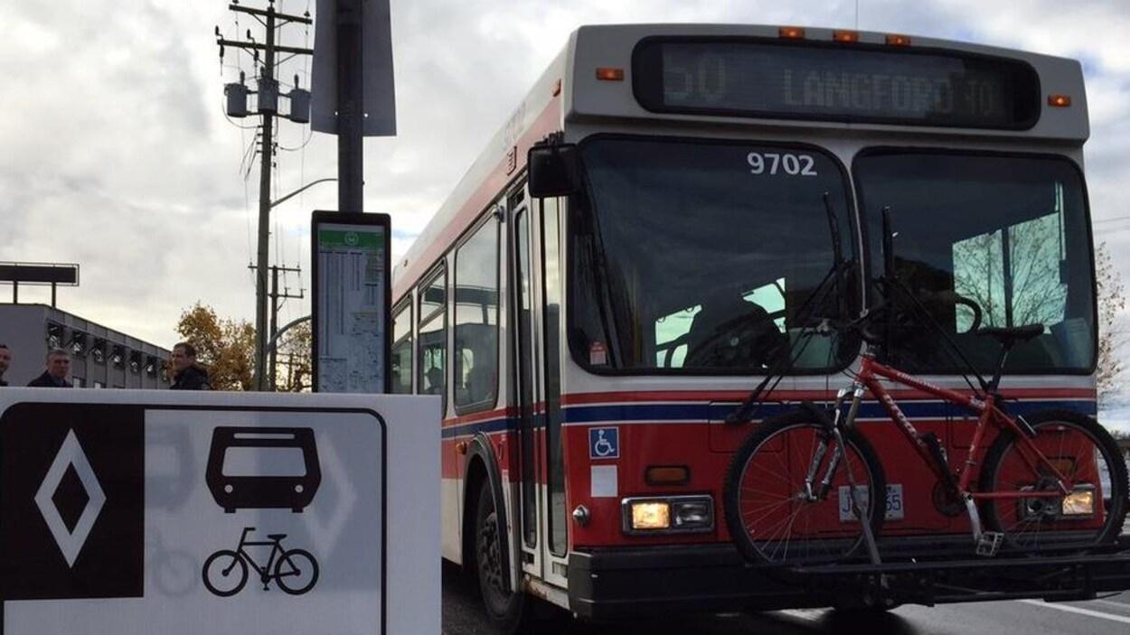 Un autobus à l'arrêt à Victoria pendant que quatre hommes se font la conversation sur le trottoir.