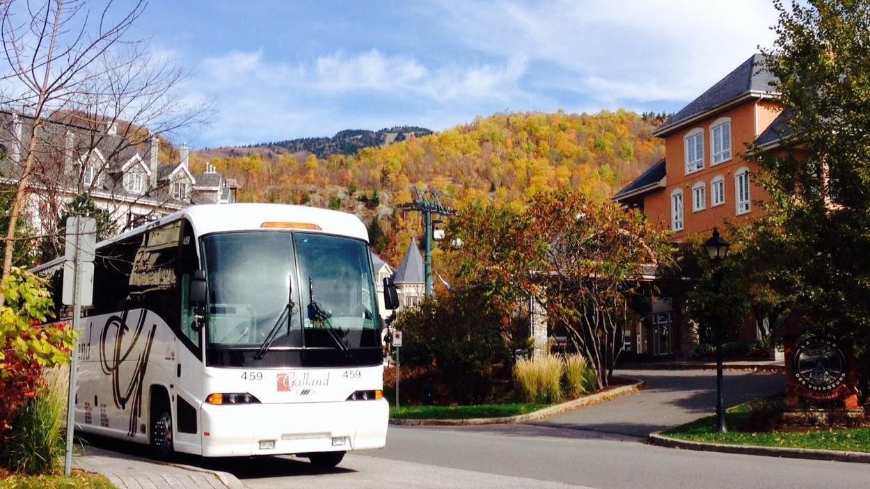 Un autocar est arrêté à un coin de rue, des montagnes en arrière-plan.