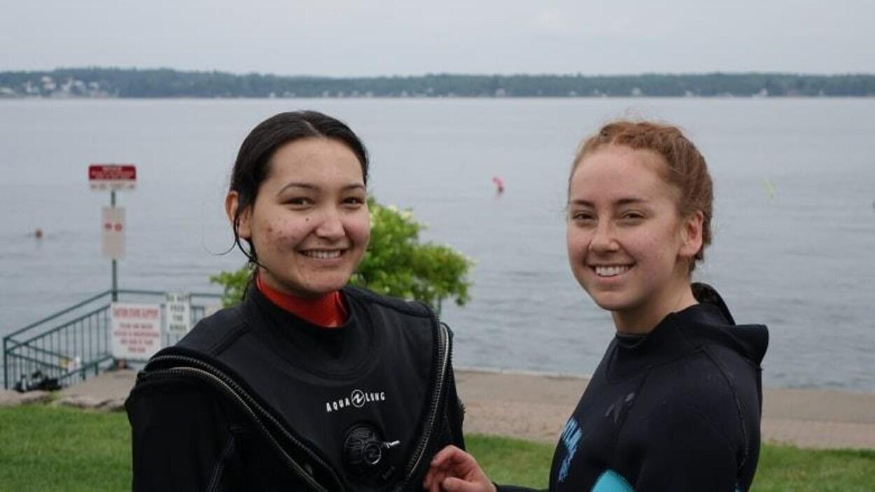 Deux jeunes inuites posent et sourient devant le fleuve Saint-Laurent vêtues d'habits de plongée.