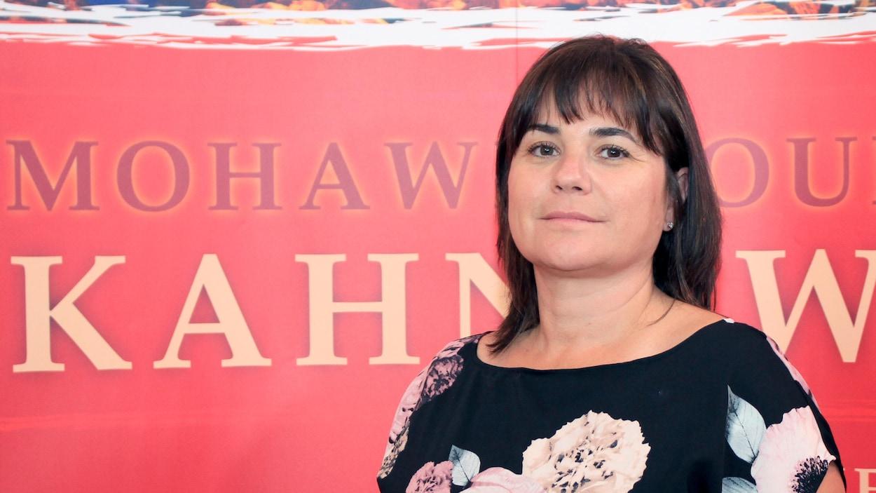 La cheffe du Conseil mohawk de Kahnawake, Gina Deer, posant devant une affiche avec l'inscription Kahnawake.