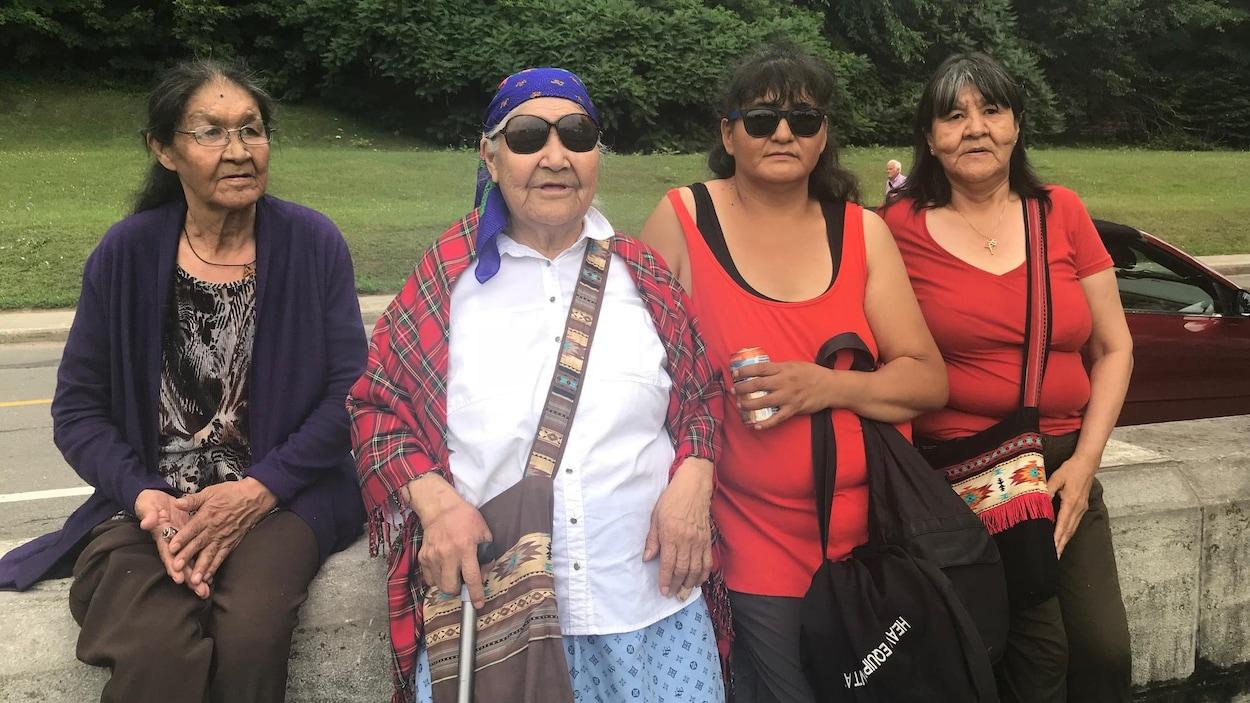 Quatre femmes autochtones sont assises sur un muret près de la basilique de Sainte-Anne-de-Beaupré.