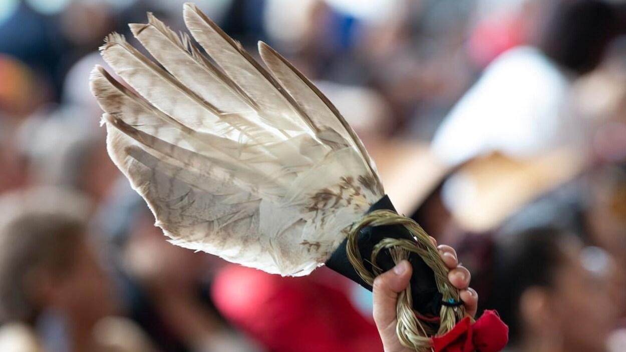 Une plume d'aigle sur laquelle est attachée un ruban rouge est tenue pendant les cérémonies entourant la publication du rapport de l'ENFFADA, le 3 juin dernier, à Gatineau.