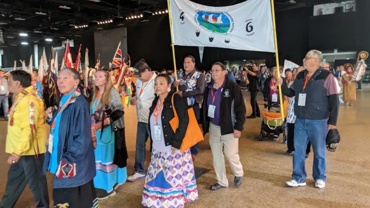 Des aînés autochtones défilent lors d'un rassemblement, des drapeaux et des banderoles à la main.