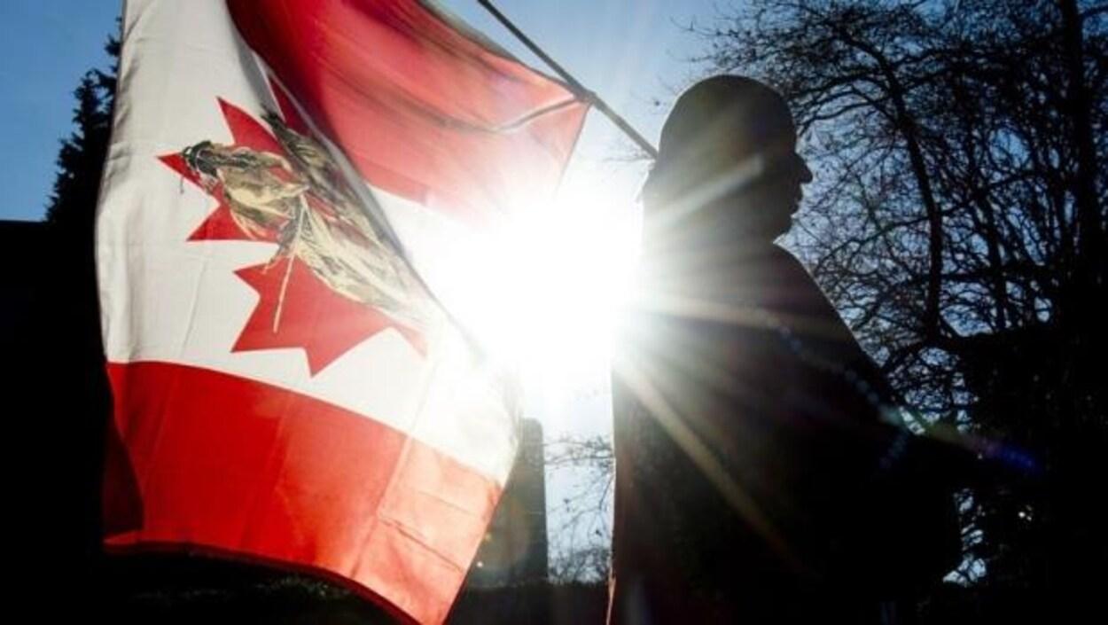 Un membre des Premières Nations tient un drapeau canadien orné d'un dessin de guerrier autochtone. Le cliché est pris en contre-jour.
