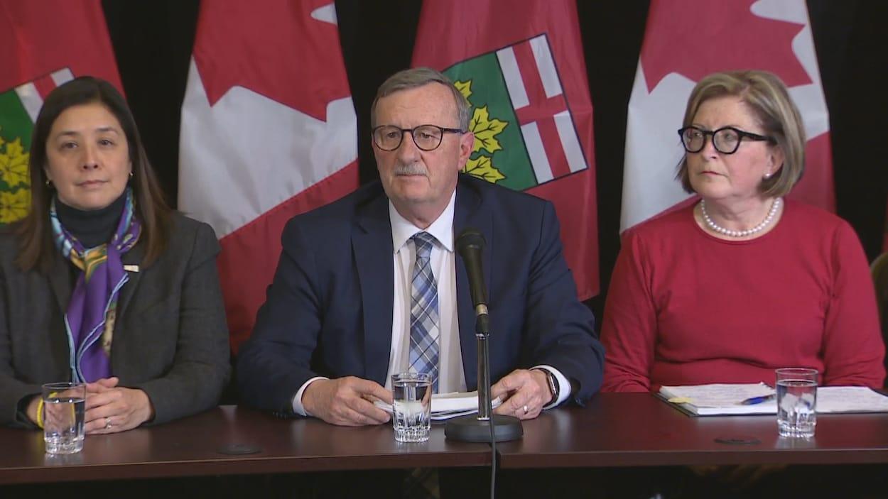 Trois personnes devant des drapeaux dans une salle de presse.
