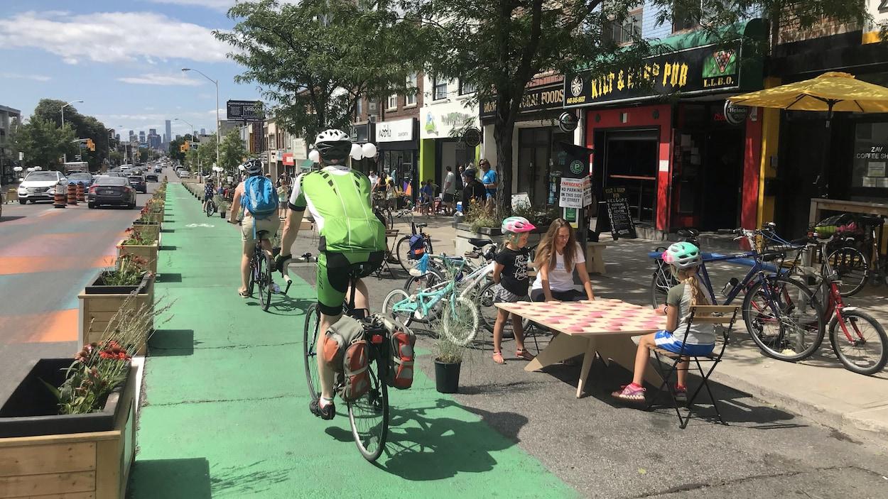 Des cyclistes sur une piste cyclable avec des enfants qui jouent à côté sur un jeu de dames gégants avec un parent.