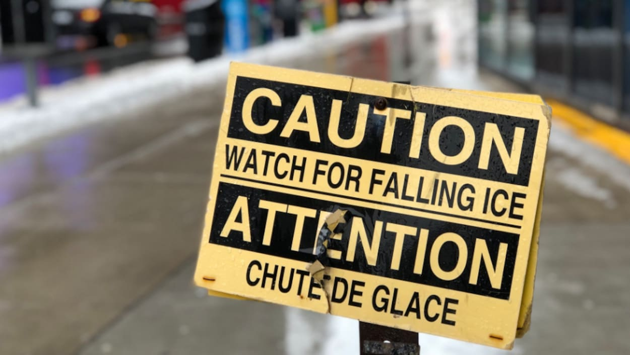 Photo d'une affiche d'avertissement jaune et noire qui dit «Attention, chute de glace»