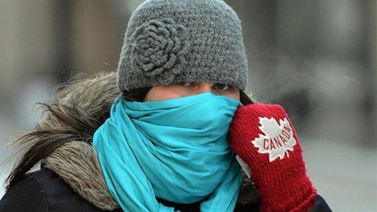 Une femme se couvrant le visage par temps froid.