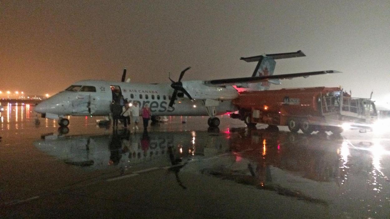 Photo d'un camion-citerne immobilisé à côté d'un avion dont la carlingue montre des dommages importants.