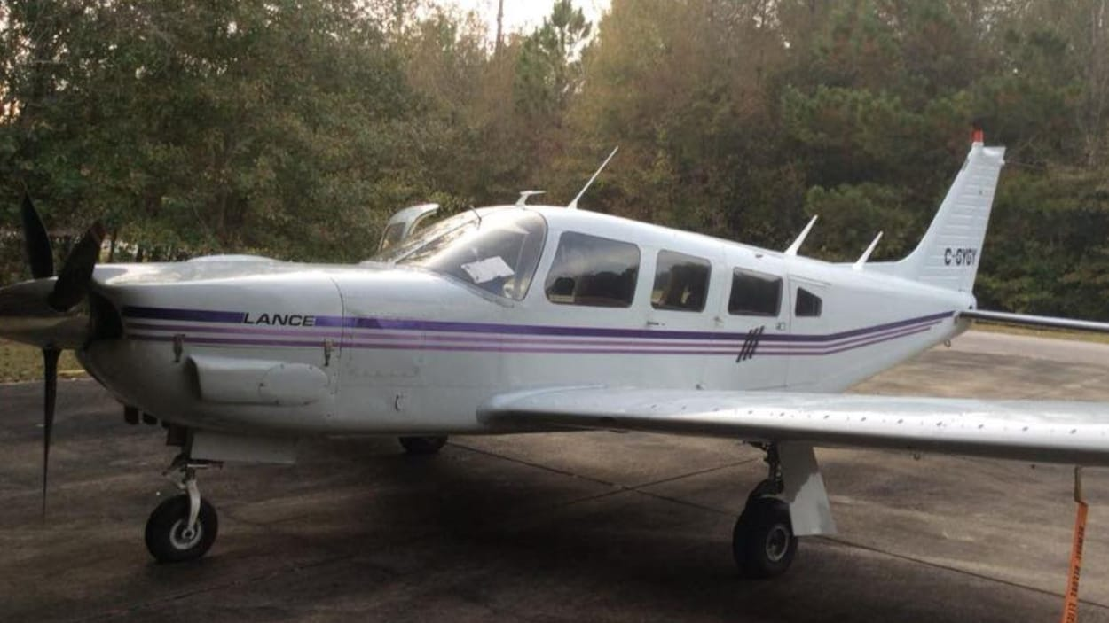 Un petit avion monomoteur garé sur la piste de décollage, avec des arbres en arrière-plan.