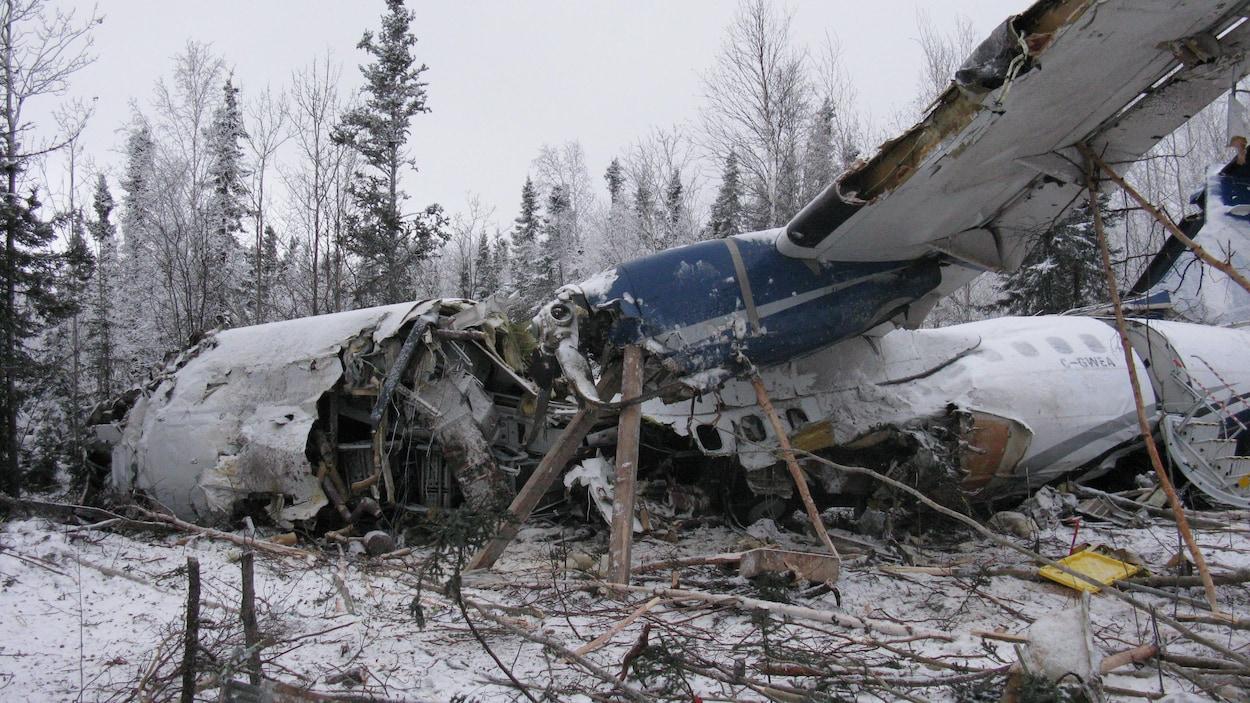 Vue de profil d'un avion bimoteur qui s'est écrasé dans une zone boisée en hiver, la carcasse et l'aile visible sont déchirées.