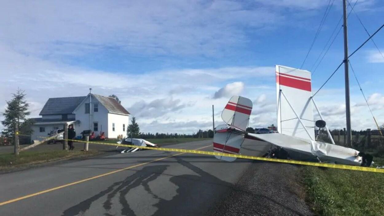 Un avion écrasé sur une route en face d'une maison.