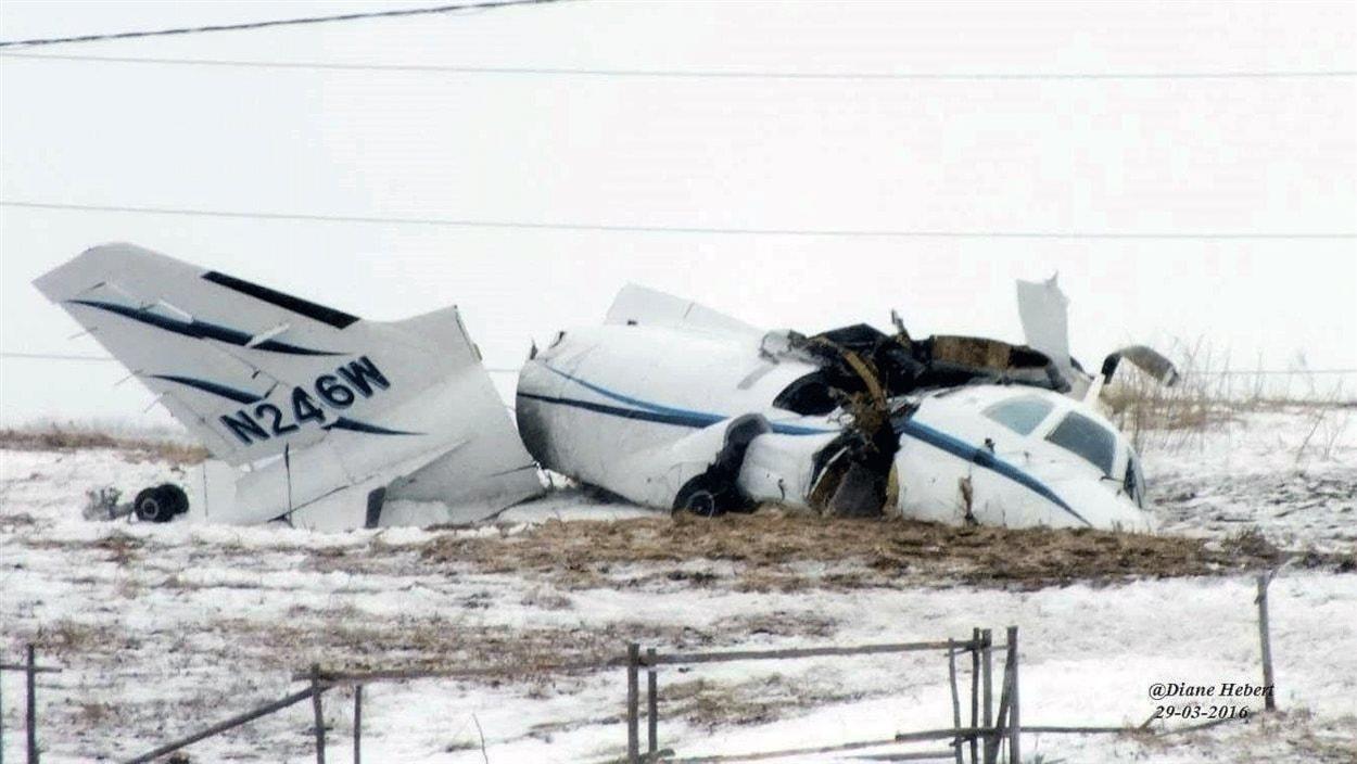 Carcasse de l'avion dans un champ enneigé.