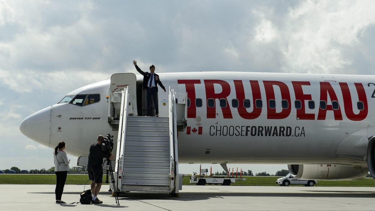 Justin Trudeau salue de la main du haut de la rampe d'accès menant à l'avion du Parti libéral du Canada.
