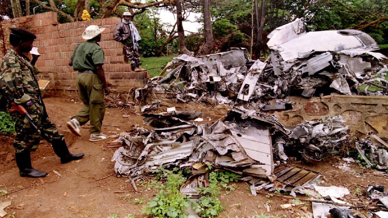 Des soldats du Front patriotique rwandais inspectent les restes de l'avion dans lequel l'ex-président rwandais  Juvénal Habyarimana a été tué, au printemps 1994, déclenchant un génocide qui a coûté la vie à 800 000 personnes.