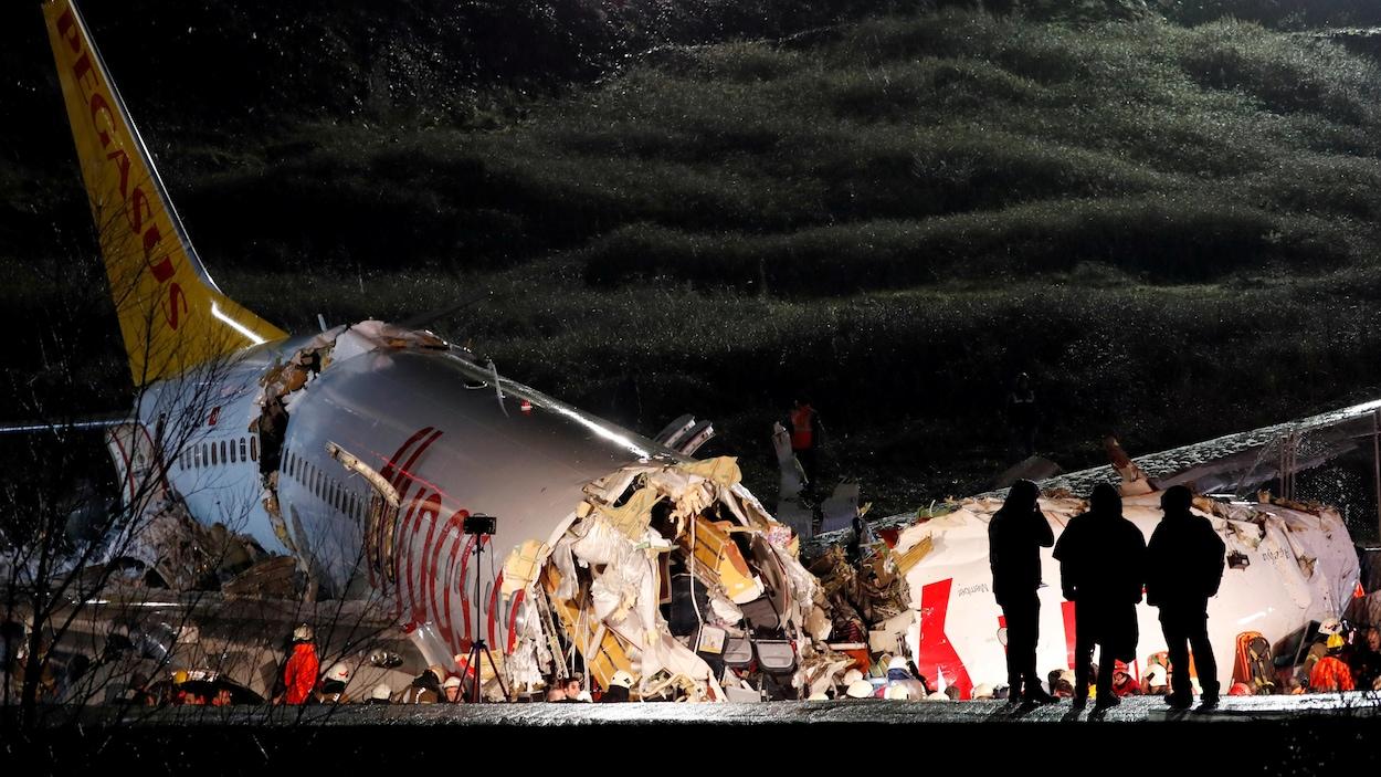 Des policiers inspectent un avion qui s'est écrasé.