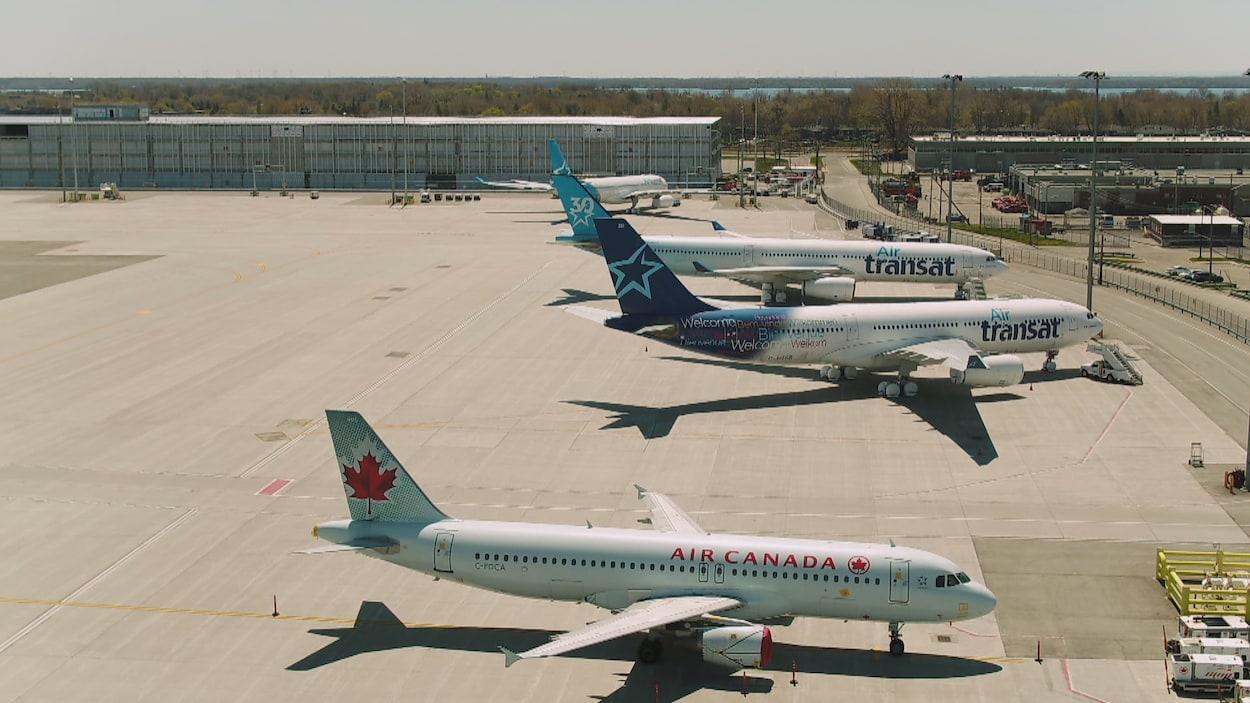 Deux avions d'Air Transat et un d'Air Canada garés sur le tarmac.