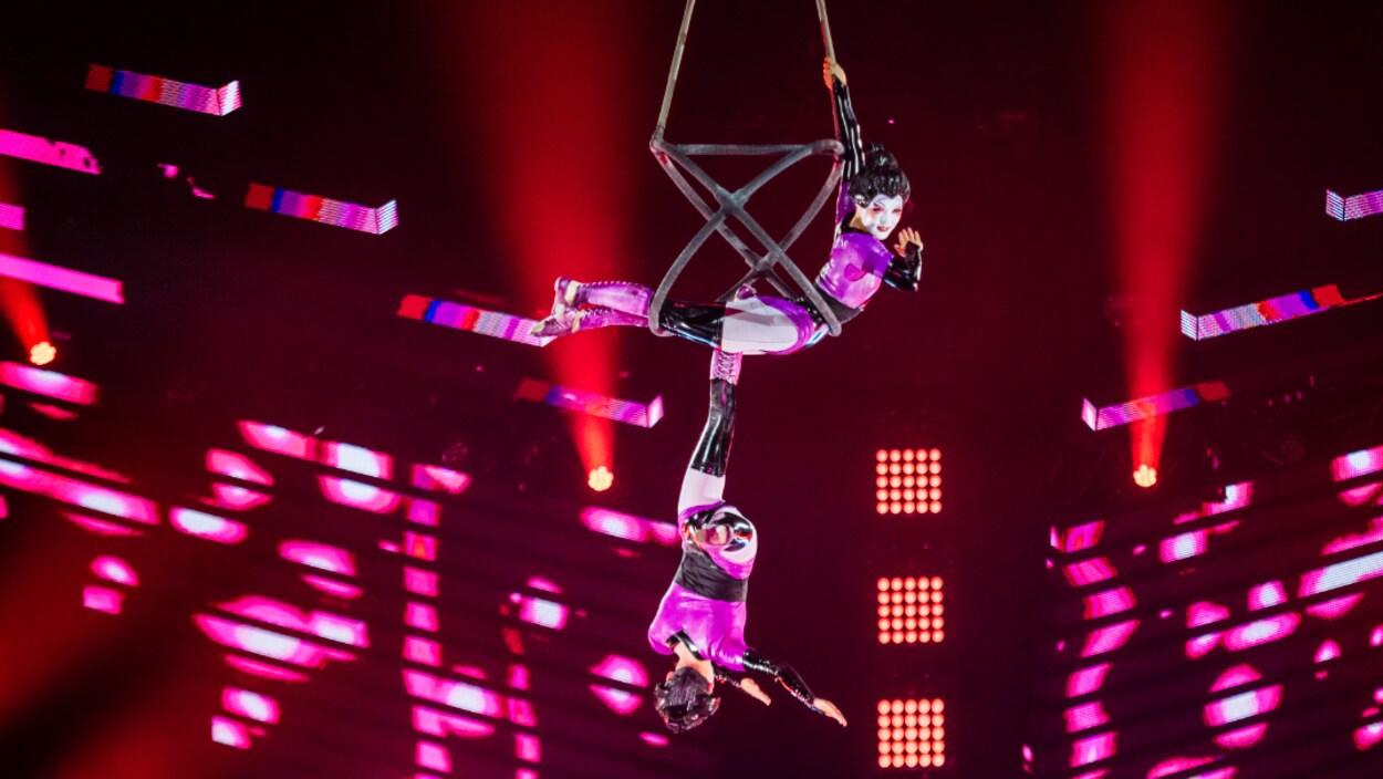 Des acrobates sont suspendues sur des cerceaux.