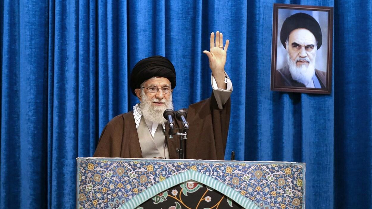 L'ayatollah lève le bras gauche pour saluer les fidèles.