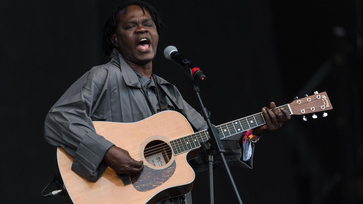Un musicien, avec sa guitare, chante au micro