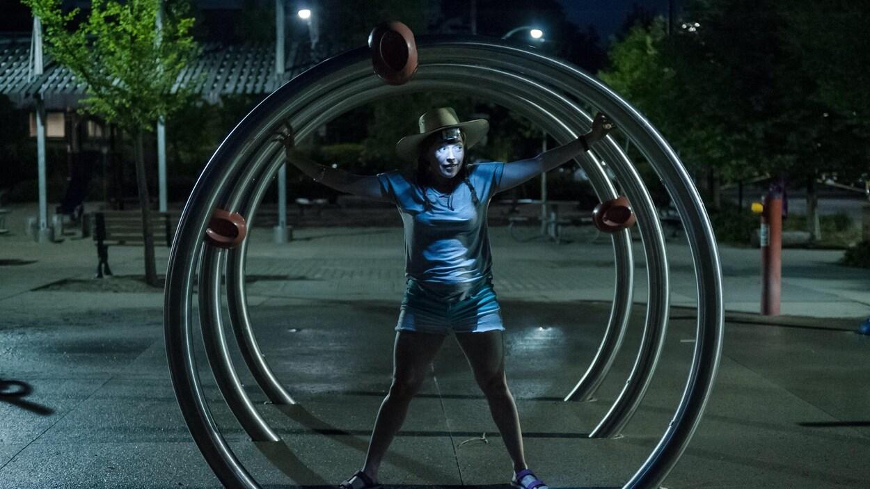 Une actrice est éclairée de nuit dans une sculpture de rue composée de 3 gros anneaux en métal.