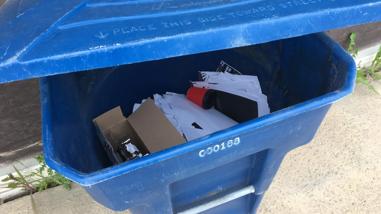 Le couvercle d'un bac de reclyclage est entrouvert, du papier et du cartons sont au fond du bac.
