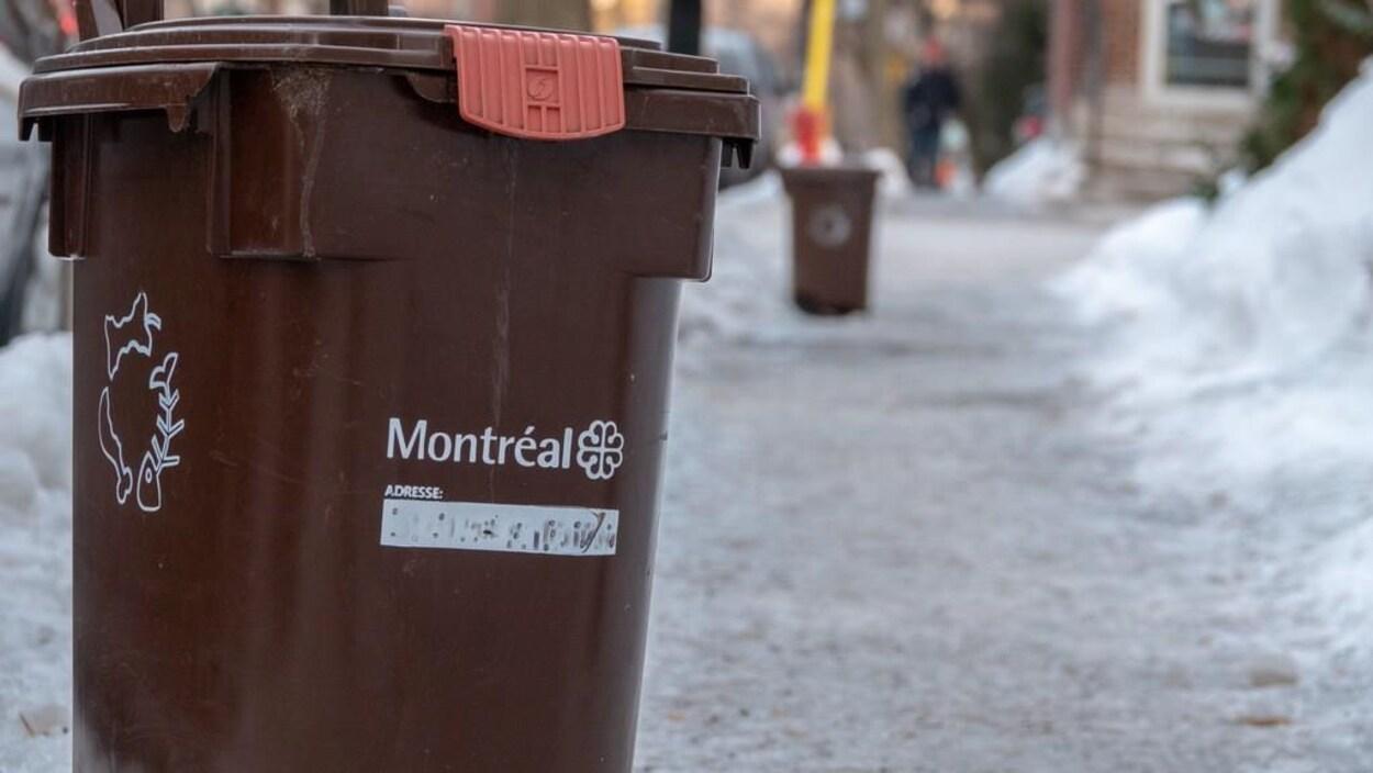 Un bac brun en bordure de la rue, en hiver.