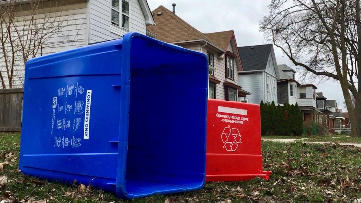 Deux bacs de recyclage devant une rangée de maisons.