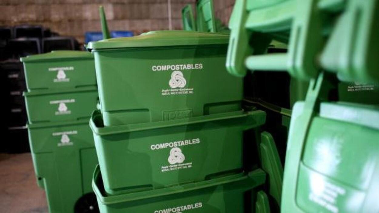 Des bacs de plastique verts empilés dans ce qui semble être un entrepôt.