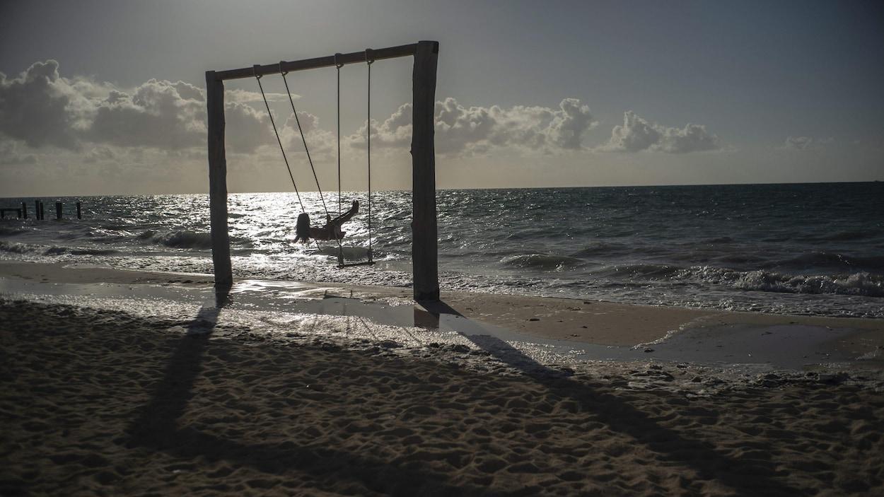 Une femme est dans une balançoire face à la mer.
