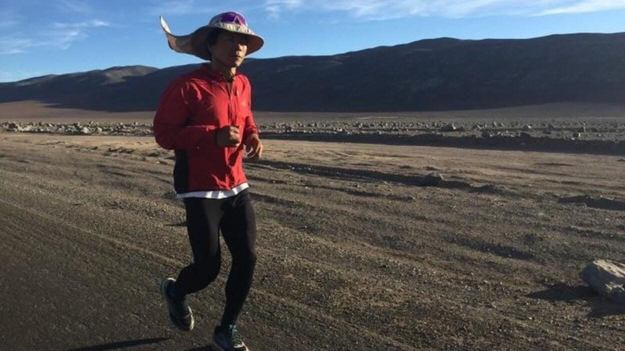 Bai Bin court dans un secteur désertique et caillouteux avec un chapeau sur la tête sous un ciel partiellement nuageux.