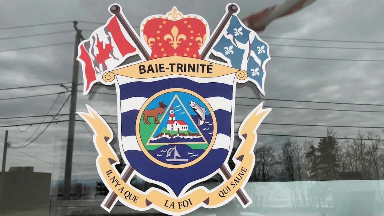 Les armoiries de Baie-Trinité sur une fenêtre.